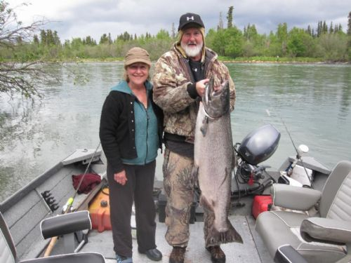 Two anglers fishing in Jim Rusk's boat on the Kenai River fishing holding a huge King salmon