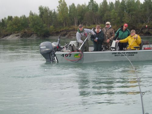 Jim Rusk fishing equipment - Kenai Fishing Guide on Drift boat with four clients, holding net to land a King Salmon