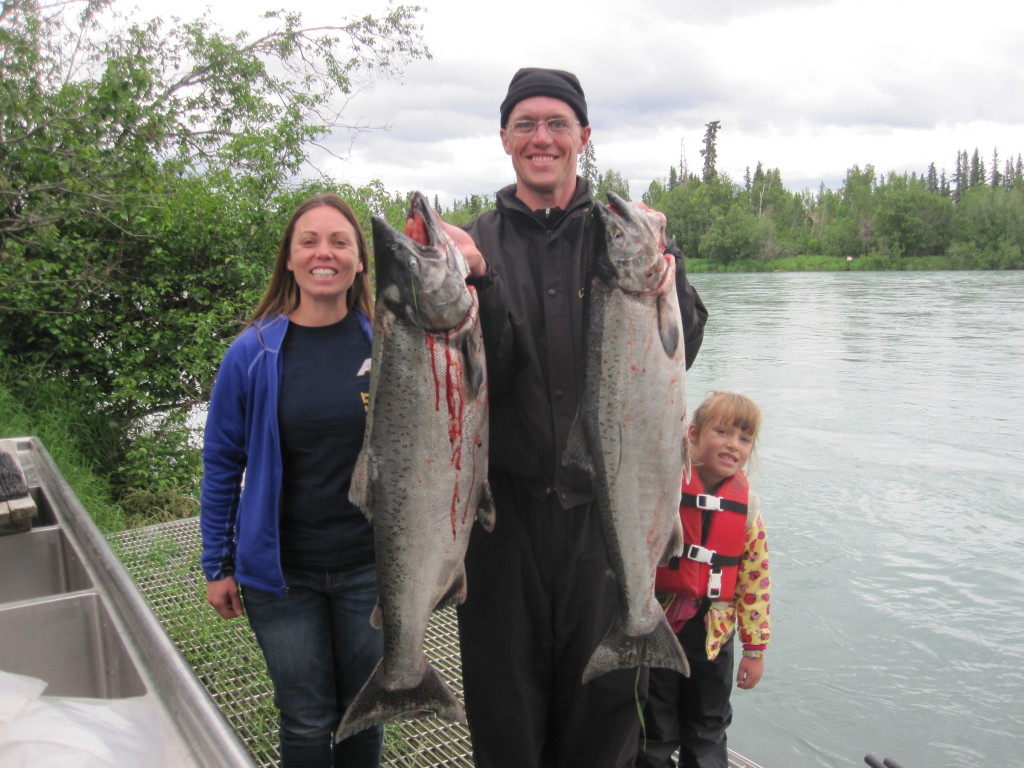Great Fishing. Two anglers and a little girl on a river bank.  Angler holding two king salmon from the Kenai River