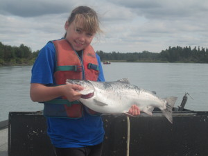 Little girl fishing with a silver salmon in her hands