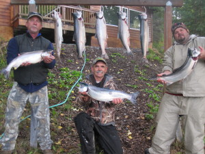 Man holding a silver salmon during September fishing 2013 on river