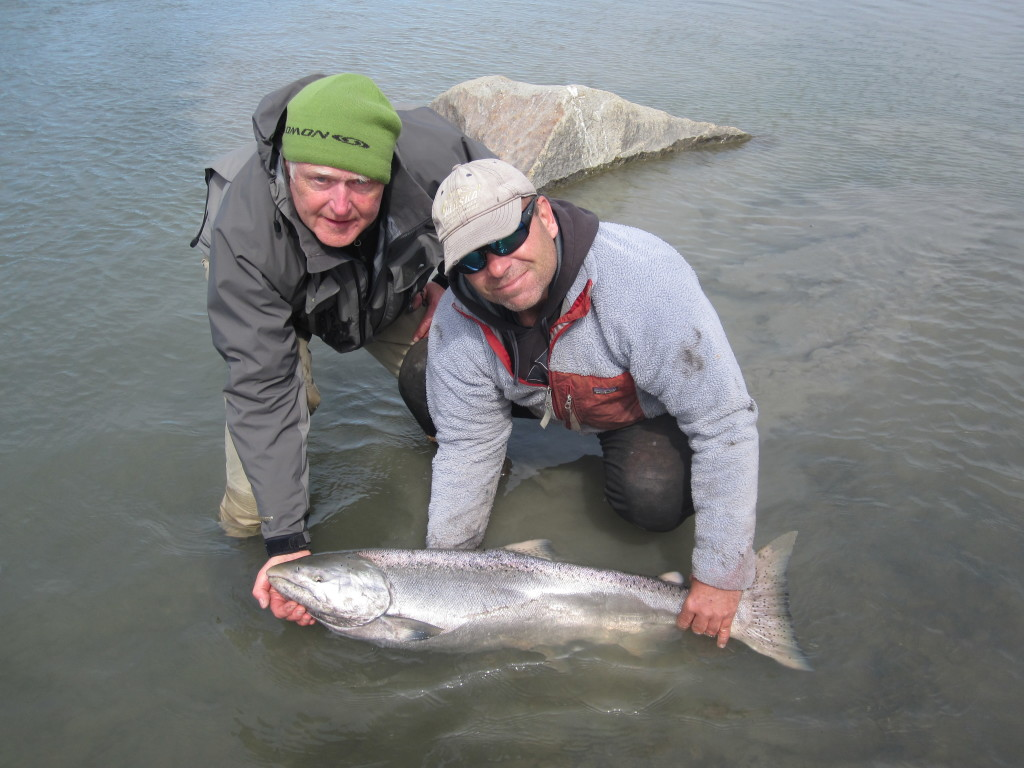 King Salmon held in the river by Jim Rusk with client watching. Alaska fishing charters
