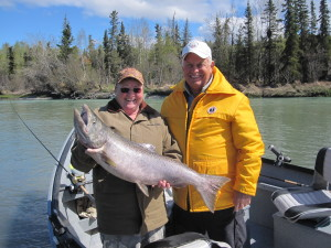 Kasilof River fishing - Two anglers holding a huge King Salmon while standing in  a boat.