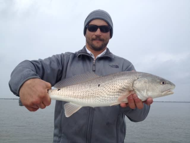 Kenai fishing guide's client holding a redfish  he caught