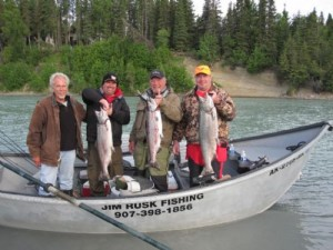 Kenai fishing guide and 3 other guys drift boat fishing in an open boat on the river holding three large salmon