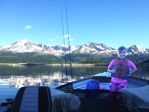 Little girl in a boat on a lake with mountains in the background