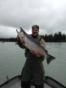 Man holding a silver salmon August  he caught. He is standing in a boat