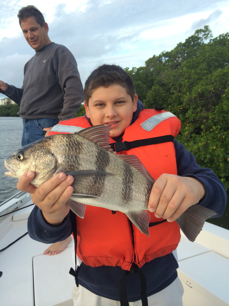 A man and his son on a boat Fort Myers fishing charter showing a Sheep Head fish