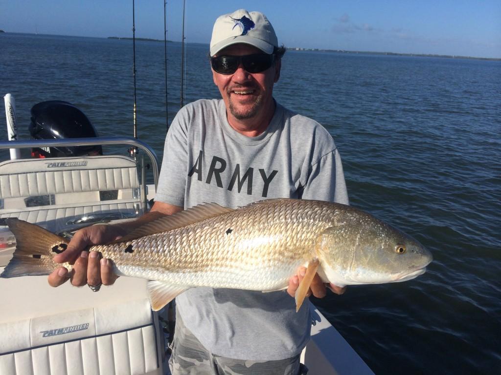 Man holding a huge redfish. Pine Island fishing