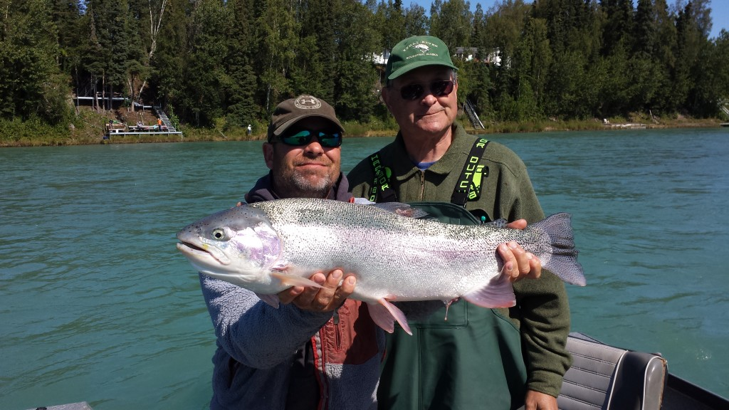 Trophy Rainbow Trout Fishing. Two men holding  a huge Trout
